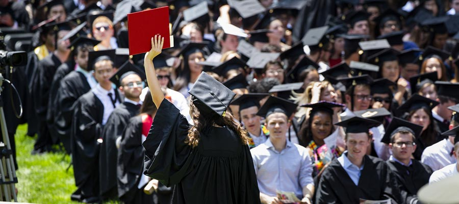 Graduate exits stage holding up her diploma; photo: Dominick Reuter